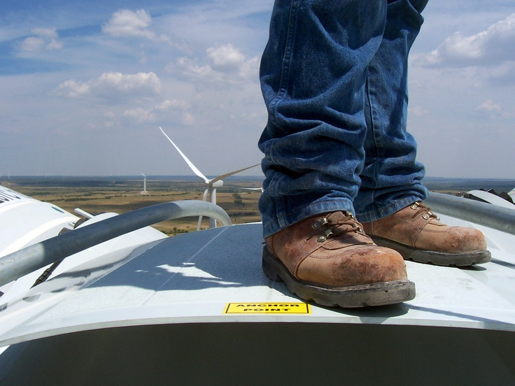 A man standing on top of a wind turbine.