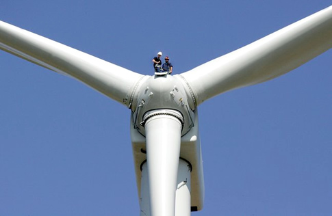 Two people standing on top of a wind turbine